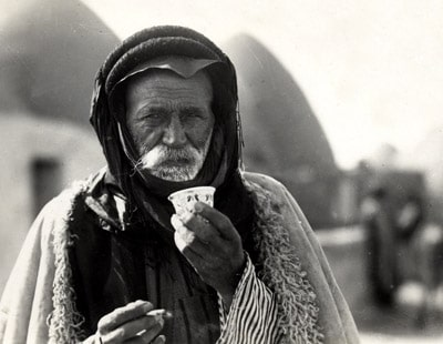 Arab Bedouin from a beehive village in Aleppo, Syria, sipping the traditional murra (bitter) coffee, 1930